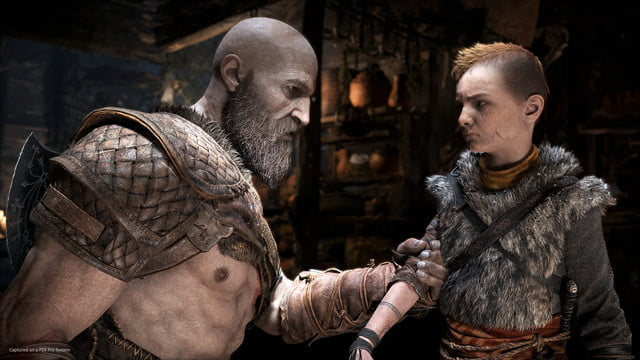 God of War Review | Kratos grabbing the arm of Atreus while speaking to him in a house