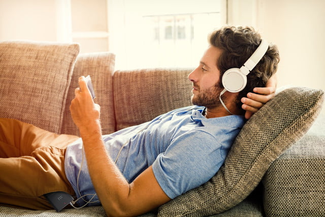 aftermaster pro fixes tv movie audio issues man on couch watches a mobile phone