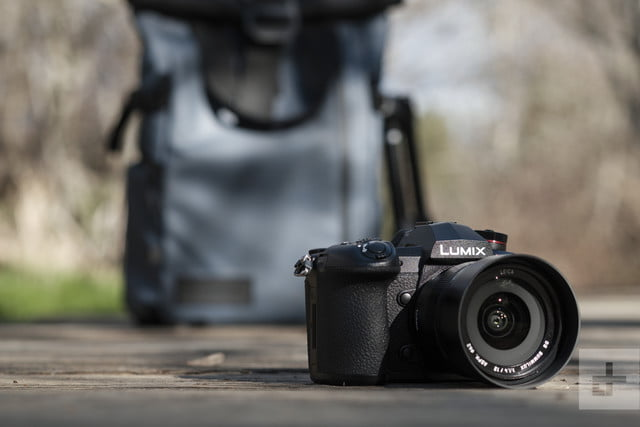 Panasonic Lumix G9 Review | Hero shot of the camera resting on the ground with a backpack in the background