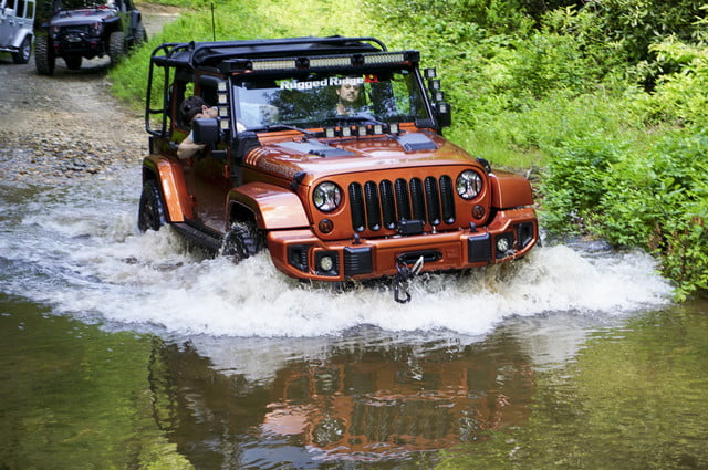 Candy-apple red Jeep Wrangler Unlimited driving through a deep portion of a river